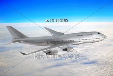 Modern Airplane Over The Clouds Stock Photo