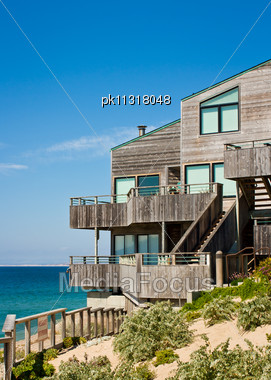 Modern Oceanfront Townhouse Adjacent To A Landscaped Sand Dune With Wooden Decks And Siding Stock Photo