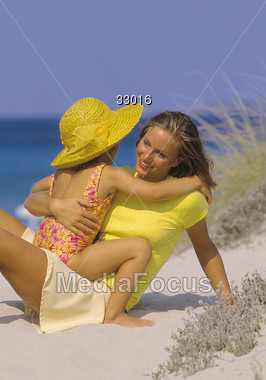 Mom is hugging daughter in the sand on the beach Stock Photo
