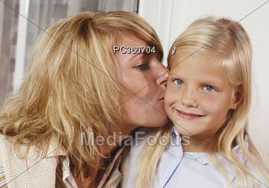 Mom Kissing Daughter on Cheek Stock Photo