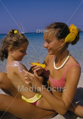 Mom rubbing lotion on her daughter at the beach Stock Photo