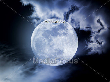 Moon In The Night Sky In Clouds Stock Photo