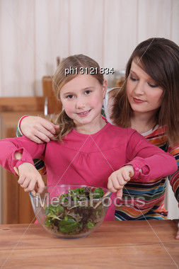 Mother And Daughter Making Salad Stock Photo