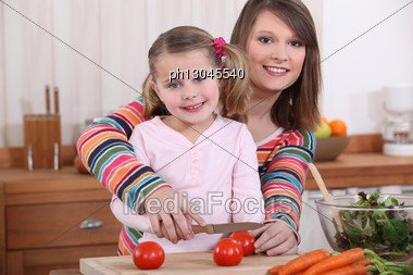 Mother And Daughter Slicing Tomatoes Stock Photo