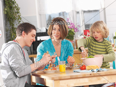 Mother With Children At Home Eating Pasta Stock Photo