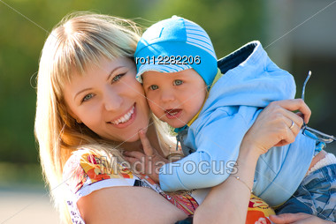 Mother Cuddling Young Son, Outdoor Portraits Stock Photo