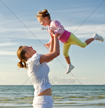 Mother And Daughter Having Fun Near The Sea Stock Photo
