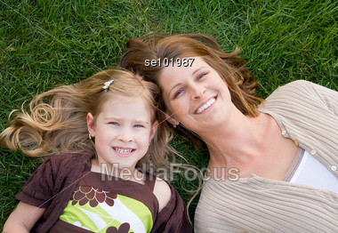 Mother and daughter laying in the grass outside Stock Photo