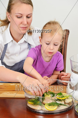 Mother And Daughter Preparing Food In Steamer. Stock Photo
