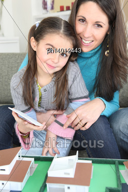 Mother And Daughter Sat By Scale Model Of Housing Stock Photo