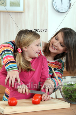Mother Teaching Her Daughter How To Cook. Stock Photo