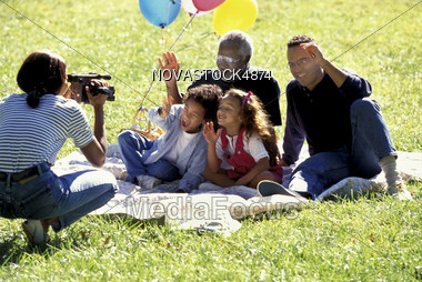 Mother Videotaping Family in Park Stock Photo