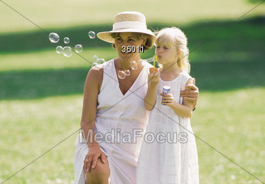 Mother with Daughter Blowing Bubbles Stock Photo