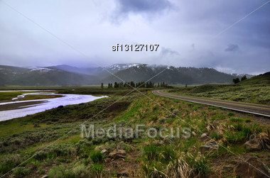 Mountain Landscape With River And Road Against A Rainy Sky Stock Photo