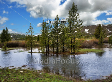 Mountain Landscape With River And Trees Against A Cloudy Sky Stock Photo