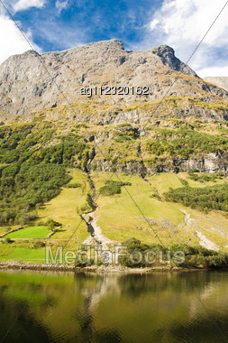Mountain Of Norwegian Fjord In Norway. Clouds And Blue Sky Stock Photo
