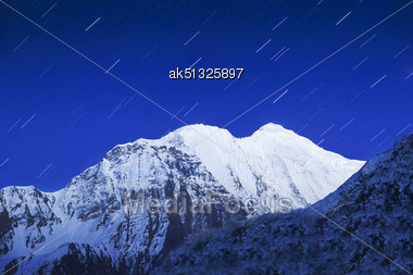 Mountain And Star Trails On The Night Sky Stock Photo