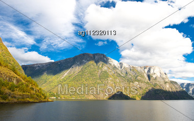 Mountains And Fiords - Norwegian Landscape. Clouds And Blue Sky Stock Photo