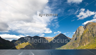 Mountains And Norwegian Fiord. Clouds And Blue Sky Stock Photo