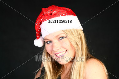 Mrs. Santa Dreaming About Christmas On Dark Background Stock Photo