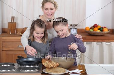 Mum And Girls Making Pancakes Stock Photo