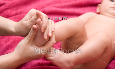 Mum Massaging Her Baby's Foot Shallow Focus Stock Photo