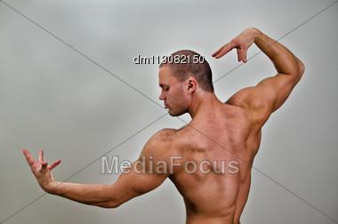 Muscular Bodybuilder Posing. On Grey Background Stock Photo