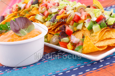 Nachos, Vegetables And Cheese Sauce On Colorful Towels Stock Photo