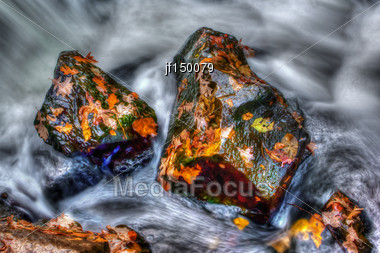 Neat Looking Rocks And Leaves With Smooth Water Running By In High Dynamic Range Stock Photo