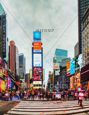 """NEW YORK CITY - MAY 11: Times Square With Tourists On May 11, 2013. Iconified As """"The Crossroads Of The World"""" It's The Brightly Illuminated Hub Of The Broadway Theater District, One Of The World's Bu Stock Photo"""