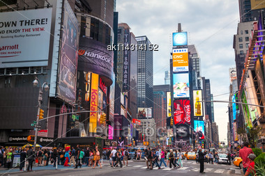 """NEW YORK CITY - MAY 11: Times Square With Tourists On May 11, 2013. Iconified As """"The Crossroads Of The World"""" It's The Brightly Illuminated Hub Of The Broadway Theater District Stock Photo"""