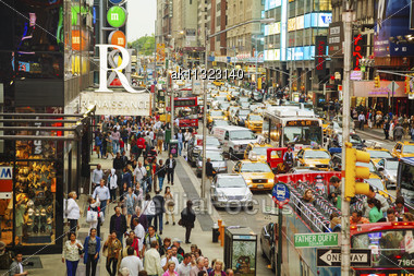 "NEW YORK CITY - MAY 12: Times Square With Tourists On May 12, 2013. Iconified As ""The Crossroads Of The World"" It's The Brightly Illuminated Hub Of The Broadway Theater District, One Of The World's Bu Stock Photo"