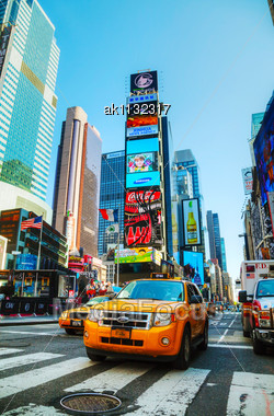 NEW YORK CITY - MAY 12: Yellow Taxis At Times Square With The Tourists On May 12, 2013 In New York. Yellow Cars Serve As Taxis In NYC And Are Easy To Spot Among Other Vehicles Because Of Their Color Stock Photo