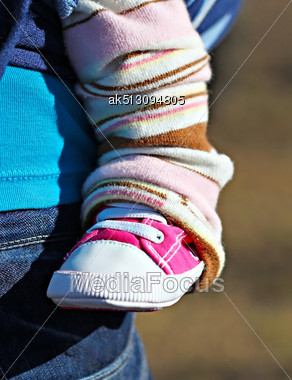Newborn Baby Leg In The Pink Shoe, In The Sling With Mother Stock Photo