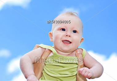 Newborn Girl Fly On Blue Sky Background Stock Photo