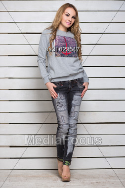 Nice Blond Woman In Gray Hoody And Black Jeans Posing Near White Wooden Wall Stock Photo