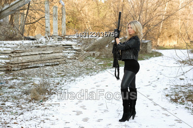 Nice Young Blonde With A Gun Outdoors Stock Photo