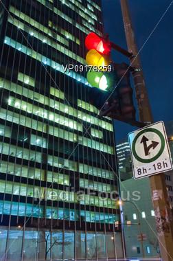 night cityscape scene with a skyscrapper and traffic light Stock Photo