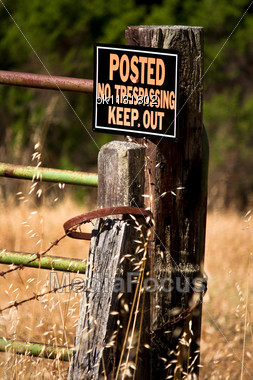 """no Trespassing Keep Out"" Sign On A Weathered Fence Post, Including Metal Straps, Barbed Wire And A Metal Gate Stock Photo"