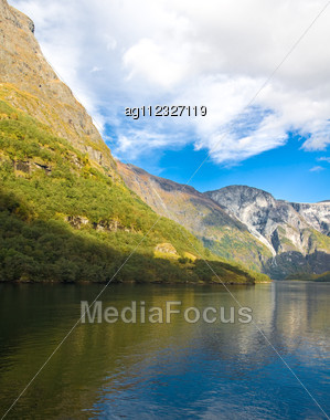 Norwegian Fjords In Autumn: Mountains, River And Blue Sky Stock Photo