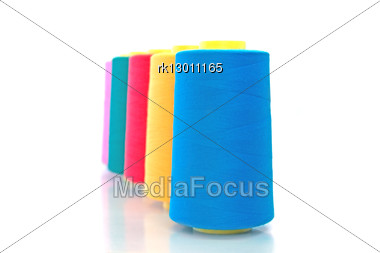 Number Of Bobbins And Thread Of Blue, Yellow, Red, Green And Pink In Isolation Stock Photo