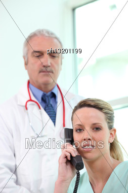 Nurse On The Telephone Whilst A Doctor Stands By Stock Photo