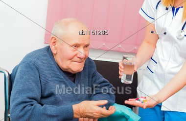 Nursing Home Assistant Giving Daily Treatment To Patient With Alzheimer's Disease Stock Photo