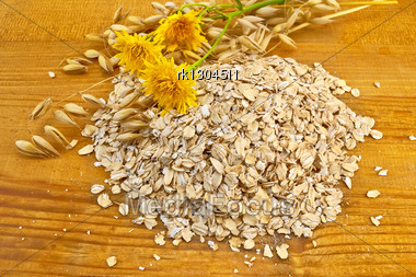 Oatmeal With Yellow Wild Flowers And Stalks Of Oats Against A Wooden Board Stock Photo