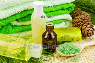Oil In A Bottle, Cedar Cones With Branch, Two Green Homemade Soap, Towels, Salt In The Wooden Spoon, Lotion, Shower Gel On A Bamboo Mat Stock Photo