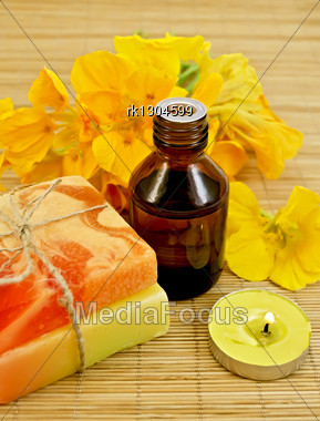 Oil In A Bottle, Two Homemade Soaps, Nasturtium Flowers, Yellow Candle On A Bamboo Mat Stock Photo