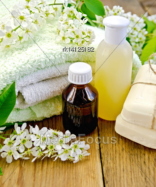 Oil And Lotion Bottles, Soap, Flowers Bird Cherry, A Towel On The Background Of Wooden Boards Stock Photo