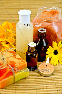 Oil And Lotion Bottles, Two Homemade Soap, Orange Bath Salt, Nasturtium And Marigold Flowers, A Candle On A Bamboo Mat Stock Photo