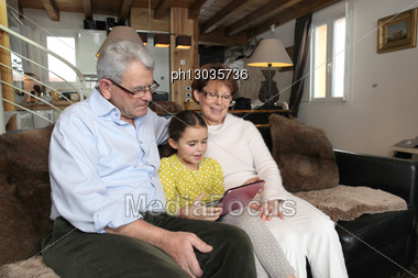 Old Couple Sat With Their Granddaughter Stock Photo