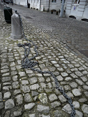 Old Downtown Street With Cobblestone And Big Long Chain On The Street. Stock Photo